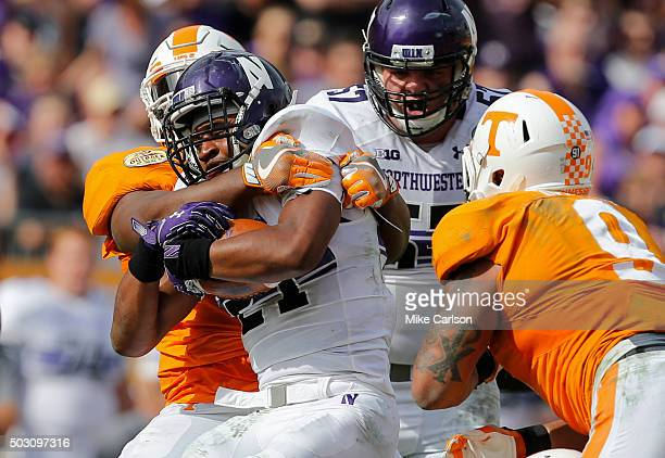 Justin Jackson of the Northwestern Wildcats is tackled by Kahlil McKenzie of the Tennessee Volunteers as Matt Frazier of the Northwestern Wildcats...