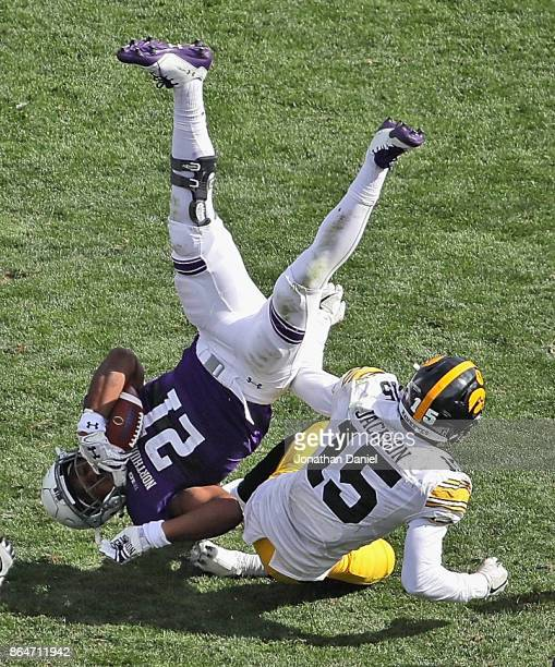 Justin Jackson of the Northwestern Wildcats is upended by Joshua Jackson of the Iowa Hawkeyes at Ryan Field on October 21, 2017 in Evanston,...