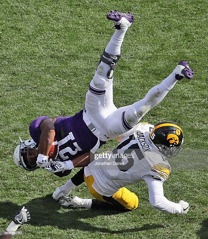 Justin Jackson #21 of the Northwestern Wildcats is upended by Joshua Jackson #15 of the Iowa Hawkeyes at Ryan Field on October 21, 2017 in Evanston, Illinois. Northwestern defeated Iowa 17-10 in overtime.