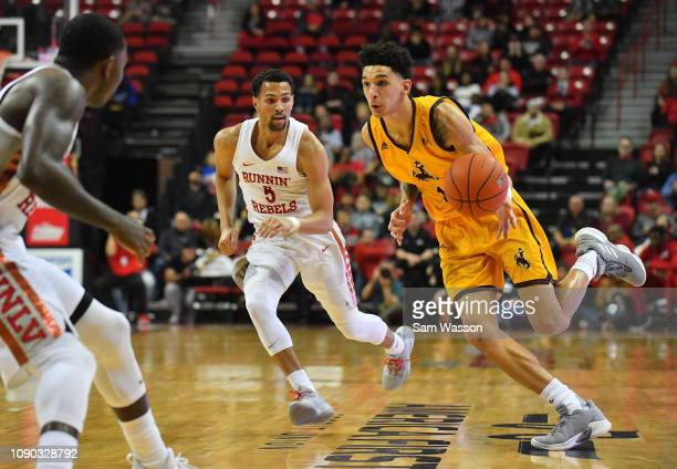 Justin James of the Wyoming Cowboys drives against Noah Robotham of the UNLV Rebels during their game at the Thomas Mack Center on January 05 2019 in...