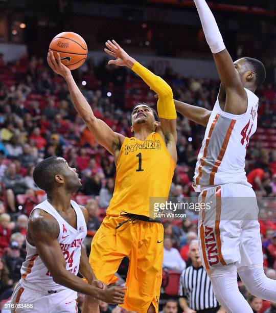Justin James of the Wyoming Cowboys shoots against Jordan Johnson and Brandon McCoy of the UNLV Rebels during their game at the Thomas Mack Center on...