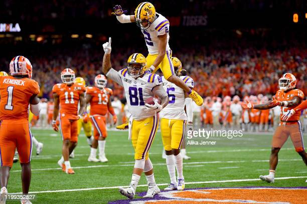 Justin Jefferson jumps on Thaddeus Moss of the LSU Tigers after he scores on a 6yard touchdown pass from Joe Burrow during the second quarter of the...