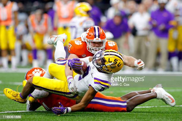 Justin Jefferson of the LSU Tigers is tackled by Denzel Johnson of the Clemson Tigers and James Skalski of the Clemson Tigers in the College Football...