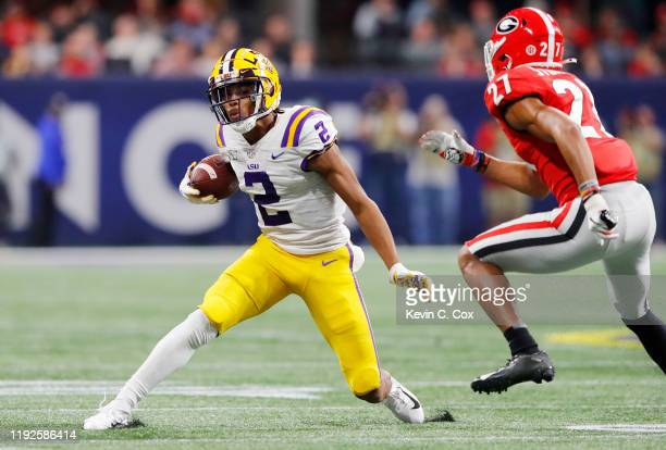 Justin Jefferson of the LSU Tigers runs with the ball against Eric Stokes of the Georgia Bulldogs in the second half during the SEC Championship game...