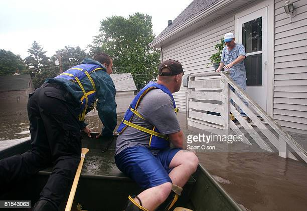 Justin Jensen of the Cedar Rapids Fire Department and Jake Siggins of the Lisbon Iowa Fire Department prepare to resuce Tom Van Hoe from his flooded...