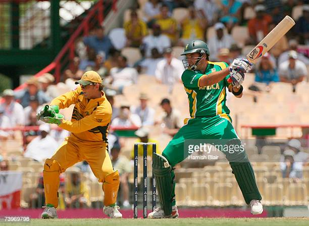 Justin Kemp of South Africa hits out watched by Adam Gilchrist of Australia during the ICC Cricket World Cup Semi Final match between Australia and...