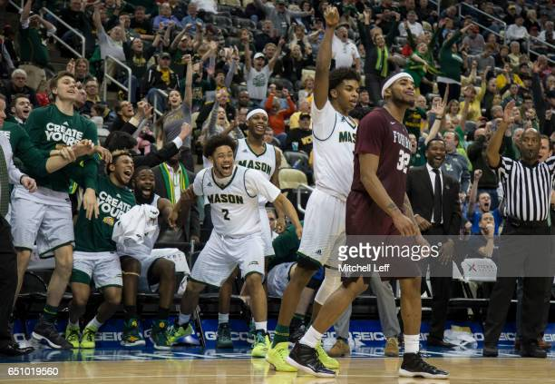 Justin Kier of the George Mason Patriots reacts after a made basket along with teammates Kameron Murrell, Ian Boyd, and Karmari Newman in front of...