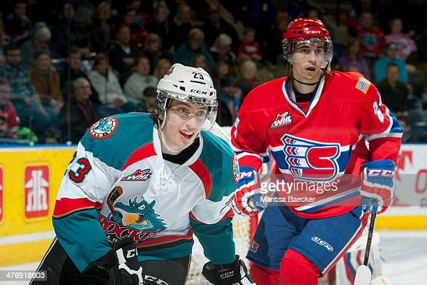 Justin Kirkland of the Kelowna Rockets is checked by a player of the Spokane Chiefs during the third period on March 5, 2014 at Prospera Place in...