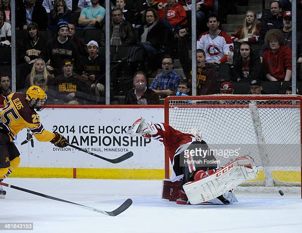 Justin Kloos of the Minnesota Golden Gophers gets the puck past Ryan Faragher of the St Cloud State Huskies for a goal during the second period of...