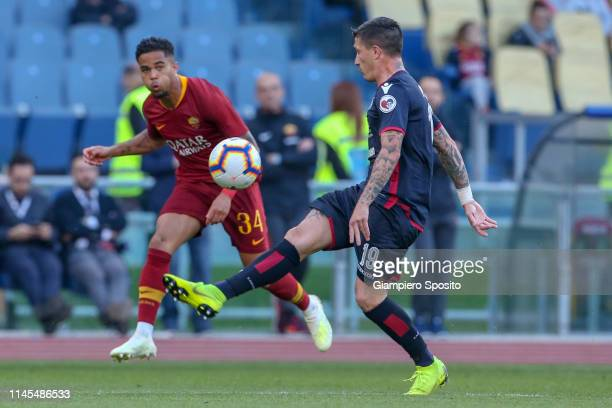 Justin Kluivert of AS Roma is challenged by Fabio Pisacane of Cagliari during the Serie A match between AS Roma and Cagliari at Stadio Olimpico on...
