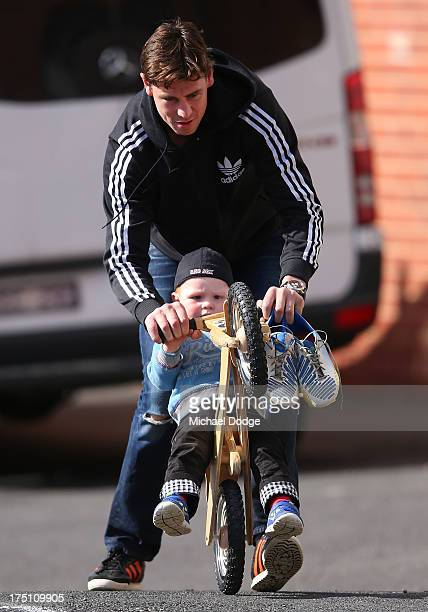 Justin Koschitzke wheels his son Jack Koschitzke out on a bike when leaving a St Kilda Saints AFL training session at Moorabbin Oval on August 1 2013...