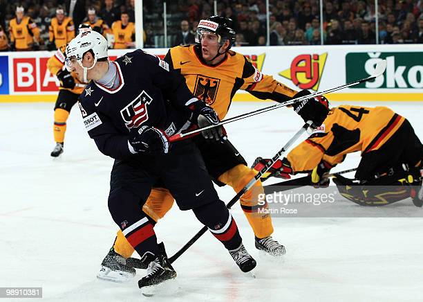 Justin Krueger of Germany tackles Chris Kreider of USA during the IIHF World Championship group D match between USA and Germany at Veltins Arena on...