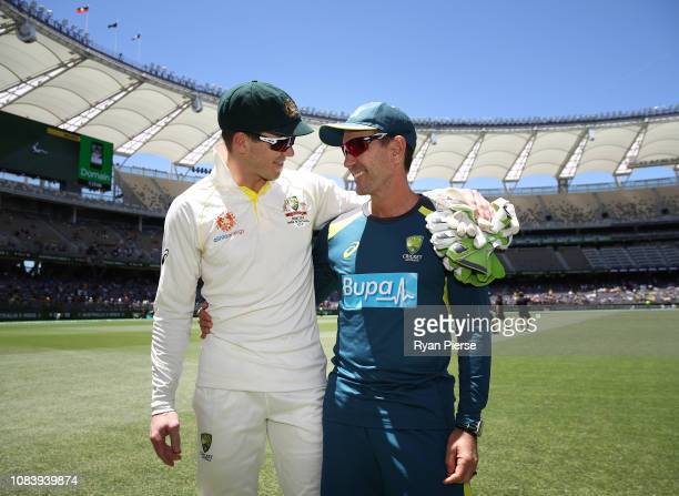 Justin Langer, coach of Australia, celebrates with Tim Paine of Australia during day five of the second match in the Test series between Australia...