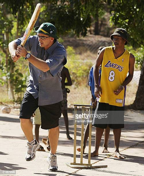 Justin Langer of Australia plays cricket with some locals on July 22 2003 during a team visit to an Aboriginal settlement on Melville Island off the...