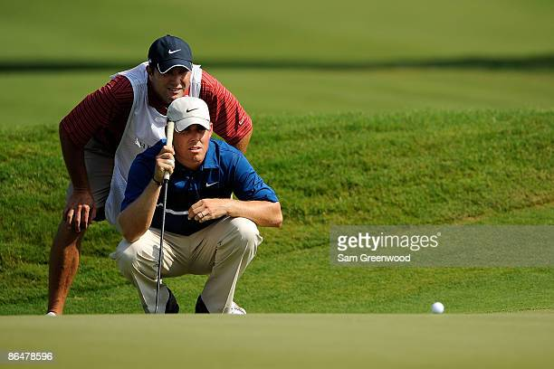 Justin Leonard lines up a putt on the 16th hole with the help of his caddie during the first round of THE PLAYERS Championship on THE PLAYERS Stadium...