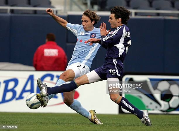 Justin Mapp of the Chicago Fire tries to get off a shot under pressure from Michael Parkhurst of the New England Revolution on April 27 2005 at...