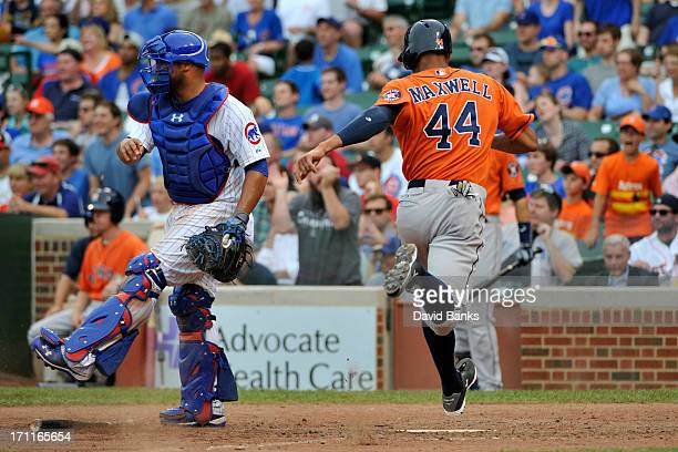 Justin Maxwell of the Houston Astros scores the goahead run as Welington Castillo of the Chicago Cubs looks on during the ninth inning on June 22...
