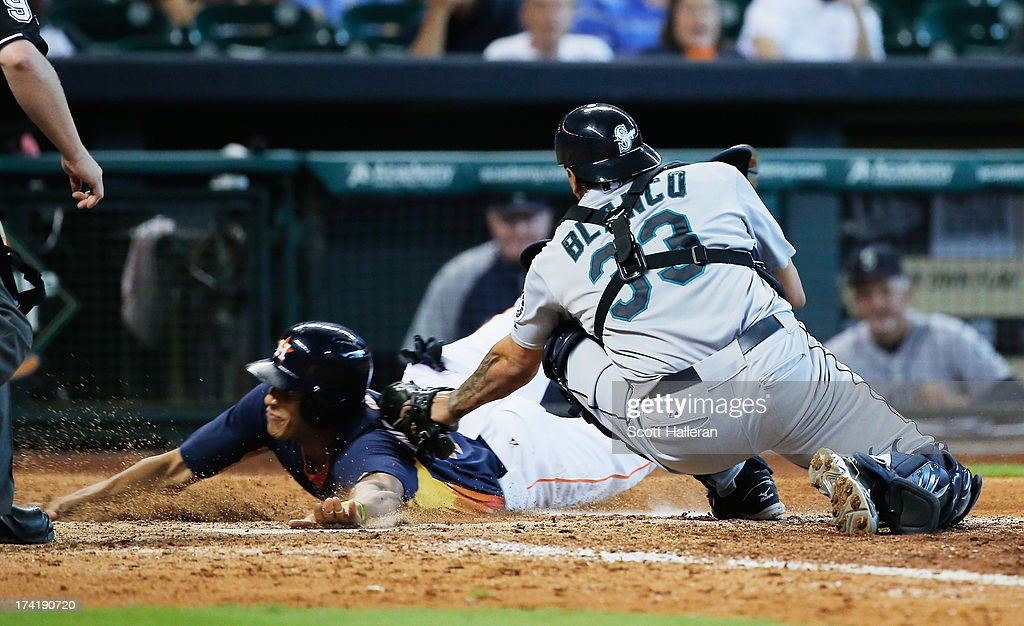 Justin Maxwell #44 of the Houston Astros slides safely into home plate in the ninth inning under the tag of Henry Blanco #33 of the Seattle Mariners at Minute Maid Park on July 21, 2013 in Houston, Texas.