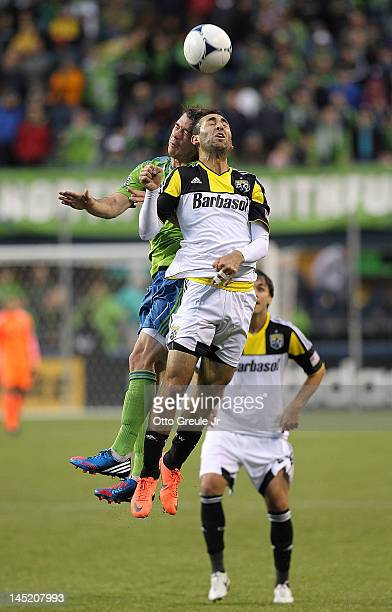 Justin Meram of the Columbus Crew heads the ball against Brad Evans of the Seattle Sounders at CenturyLink Field on May 23 2012 in Seattle Washington...