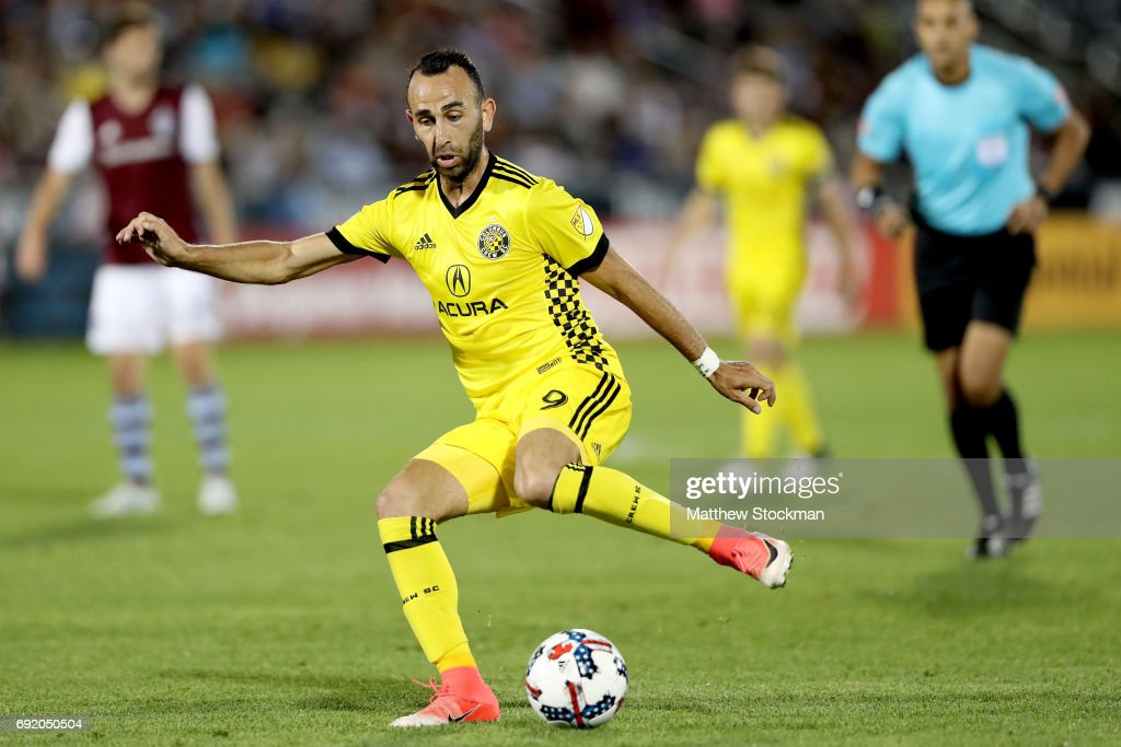 Justin Meram #9 of the Columbus Crew SC kicks a shot on goal against the Colorado Rapids at Dick's Sporting Goods Park on June 3, 2017 in Commerce City, Colorado.