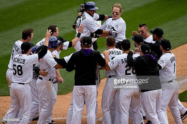 Justin Morneau of the Colorado Rockies is mobbed by teammates after hitting a walk off tworun home run in the 10th inning to defeat the San Diego...