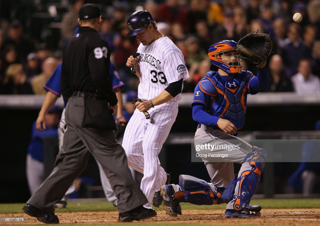 Justin Morneau #33 of the Colorado Rockies scores on a triple by Corey Dickerson #6 of the Colorado Rockies as catcher Travis d'Arnaud #15 of the New York Mets takes the late throw and umpire Will Little oversees the action as the Rockies take a 7-0 lead in the fifth inning at Coors Field on May 1, 2014 in Denver, Colorado.