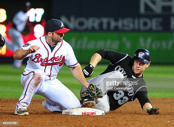 Justin Morneau of the Colorado Rockies slides in to second base for an 8th inning double against Dan Uggla of the Atlanta Braves at Turner Field on...