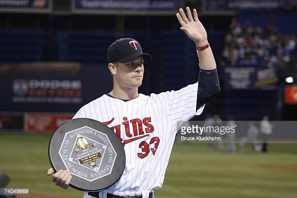 Justin Morneau of the Minnesota Twins acknowledges the crowd with his 2006 American League Most Valuable Player Award in a pregame ceremony prior to...