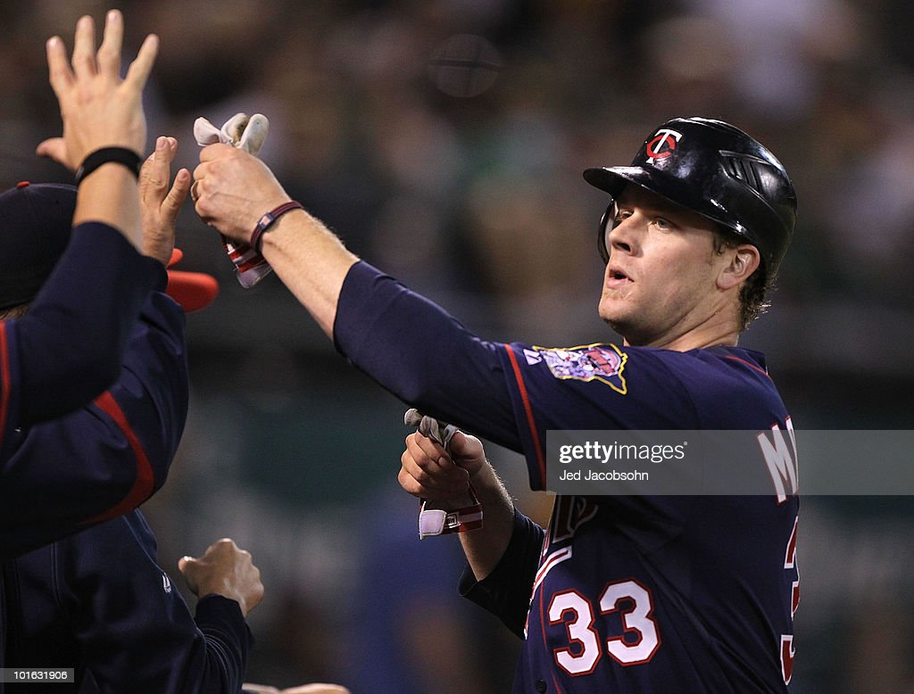 Justin Morneau #33 of the Minnesota Twins celebrates after scoring on a single by Delmon Young against the Oakland Athletics in the eleventh inning during an MLB game at the Oakland-Alameda County Coliseum on June 4, 2010 in Oakland, California.