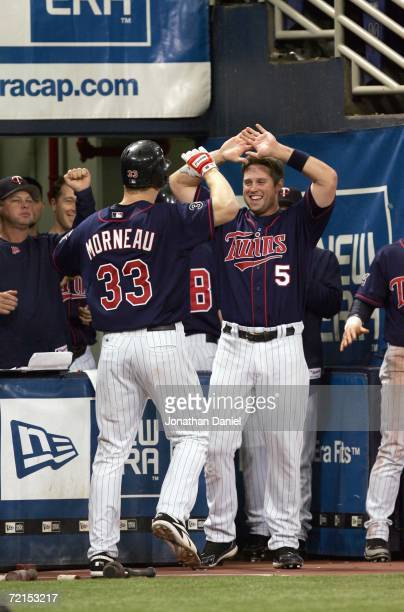 Justin Morneau of the Minnesota Twins high five Michael Cuddyer against the Oakland Athletics during game two of the American League Division Series...