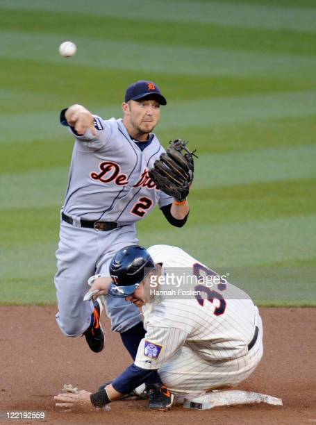 Justin Morneau of the Minnesota Twins is out at second as Ryan Raburn of the Detroit Tigers turns a double play in the first inning on August 26,...