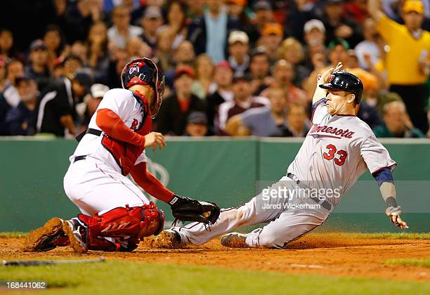 Justin Morneau of the Minnesota Twins slides safely into home plate in the sixth inning past David Ross of the Boston Red Sox during the game on May...
