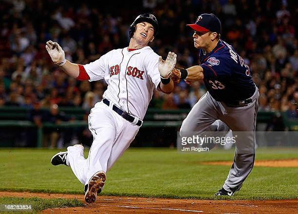 Justin Morneau of the Minnesota Twins tags out Stephen Drew of the Boston Red Sox trying to leg out an infield hit in the 5th inning at Fenway Park...