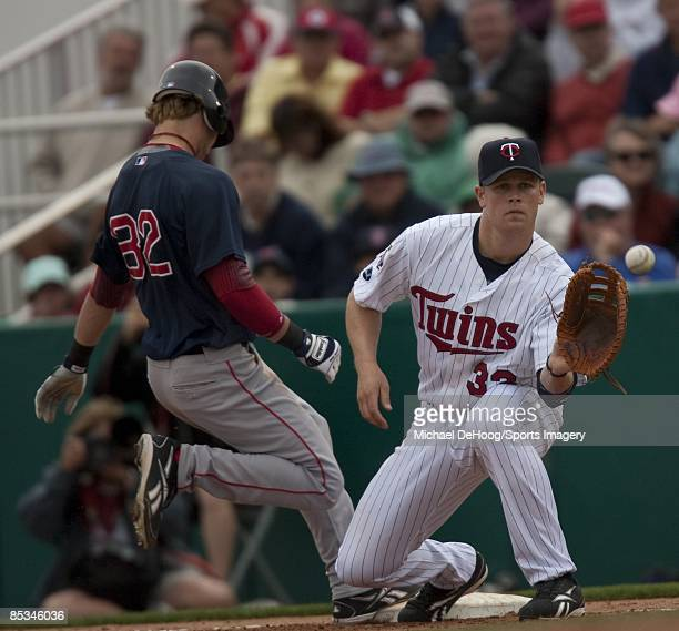Justin Morneau of the Minnesota Twins takes the throw to hold the runner close at first base during a spring training game against the Boston Red Sox...