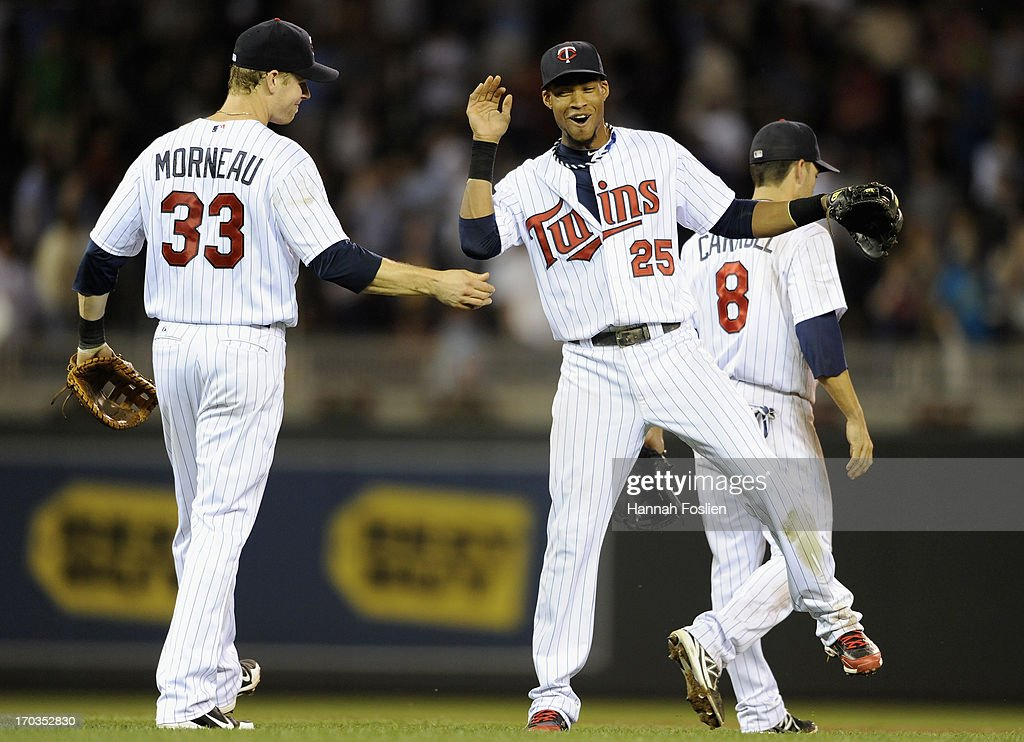 Justin Morneau #33, Pedro Florimon #25 and Jamey Carroll #8 of the Minnesota Twins celebrate a win of the game against the Philadelphia Phillies on June 11, 2013 at Target Field in Minneapolis, Minnesota. The Twins defeated the Phillies 3-2.