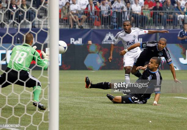 Justin Morrow and Cesar Diaz Pizarro of the San Jose Earthquakes look on as Dane Richards of the Vancouver Whitecaps FC kicks the ball past Jon Busch...