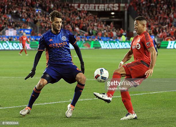 Justin Morrow of Toronto FC battles for the ball with Federico Bravo of New York City FC during the first half of an MLS Conference semifinal playoff...