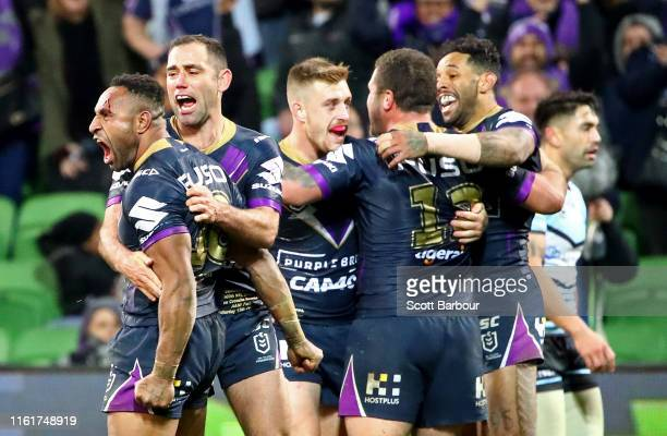 Justin Olam of the Melbourne Storm is congratulated by Cameron Smith of the Melbourne Storm and his teammates after scoring a try during the round 17...