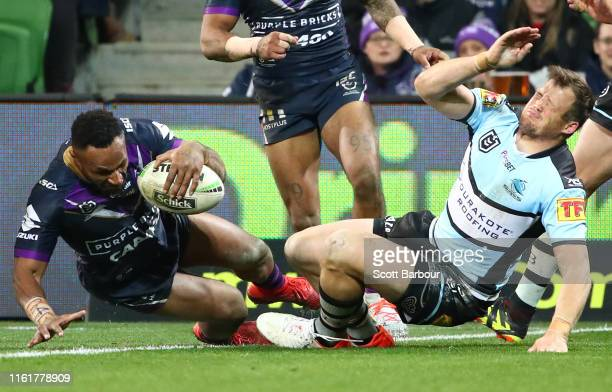 Justin Olam of the Melbourne Storm scores a try as Josh Morris of the Sharks is injured during the round 17 NRL match between the Melbourne Storm and...