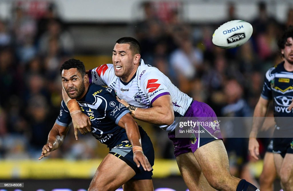 Justin O'Neil of the Cowboys gets a pass away despite the tackle of Nelson Asofa-Solomona of the Storm during the round 12 NRL match between the North Queensland Cowboys and the Melbourne Storm at 1300SMILES Stadium on May 25, 2018 in Townsville, Australia.