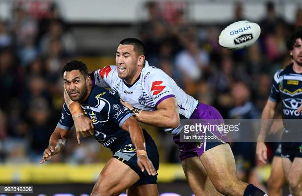 Justin O'Neil of the Cowboys gets a pass away despite the tackle of Nelson AsofaSolomona of the Storm during the round 12 NRL match between the North...