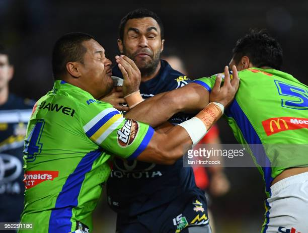 Justin O'Neil of the Cowboys is tackled by Joseph Leilua and Jordan Rapana of the Raiders during the round eight NRL match between the North...