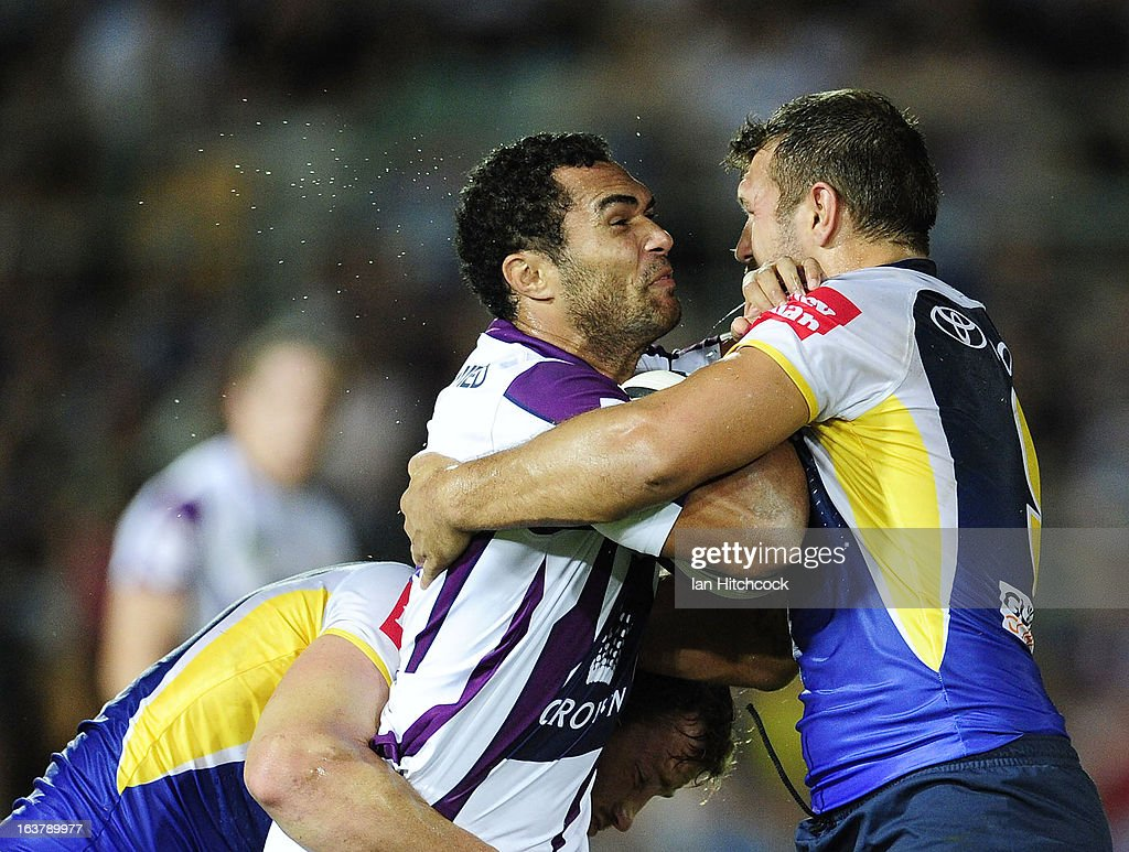 Justin O'Neil of the Storm is tackled by Scott Moore of the Cowboys during the round two NRL match between the North Queensland Cowboys and the Melbourne Storm at 1300SMILES Stadium on March 16, 2013 in Townsville, Australia.