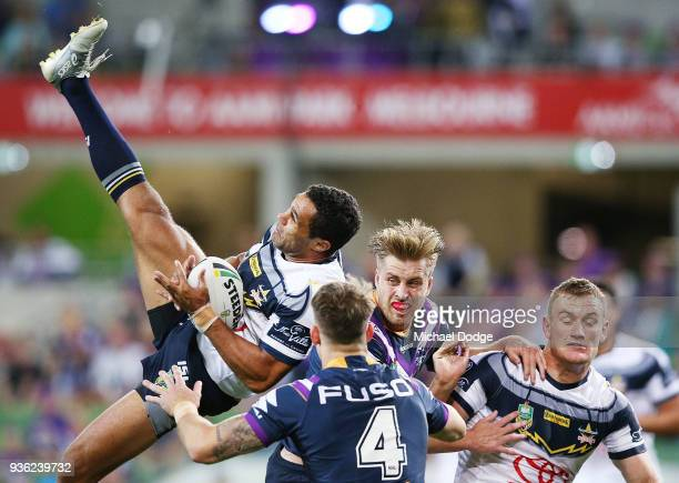 Justin O'Neill of the Cowboys catches the ball over Cameron Munster of the Storm during the round three NRL match between the Melbourne Storm and the...