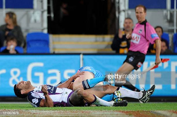Justin O'Neill of the Storm is injured in the tackle during the round 23 NRL match between the Gold Coast Titans and the Melbourne Storm at Skilled...