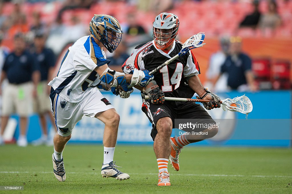 Justin Pennington #14 of the Denver Outlaws drives and is covered by Peet Poillon #57 of the Charlotte Hounds during a Major League Lacrosse game at Sports Authority Field at Mile High on June 29, 2013 in Denver, Colorado. The Outlaws led the Hounds 10-5 at the half.