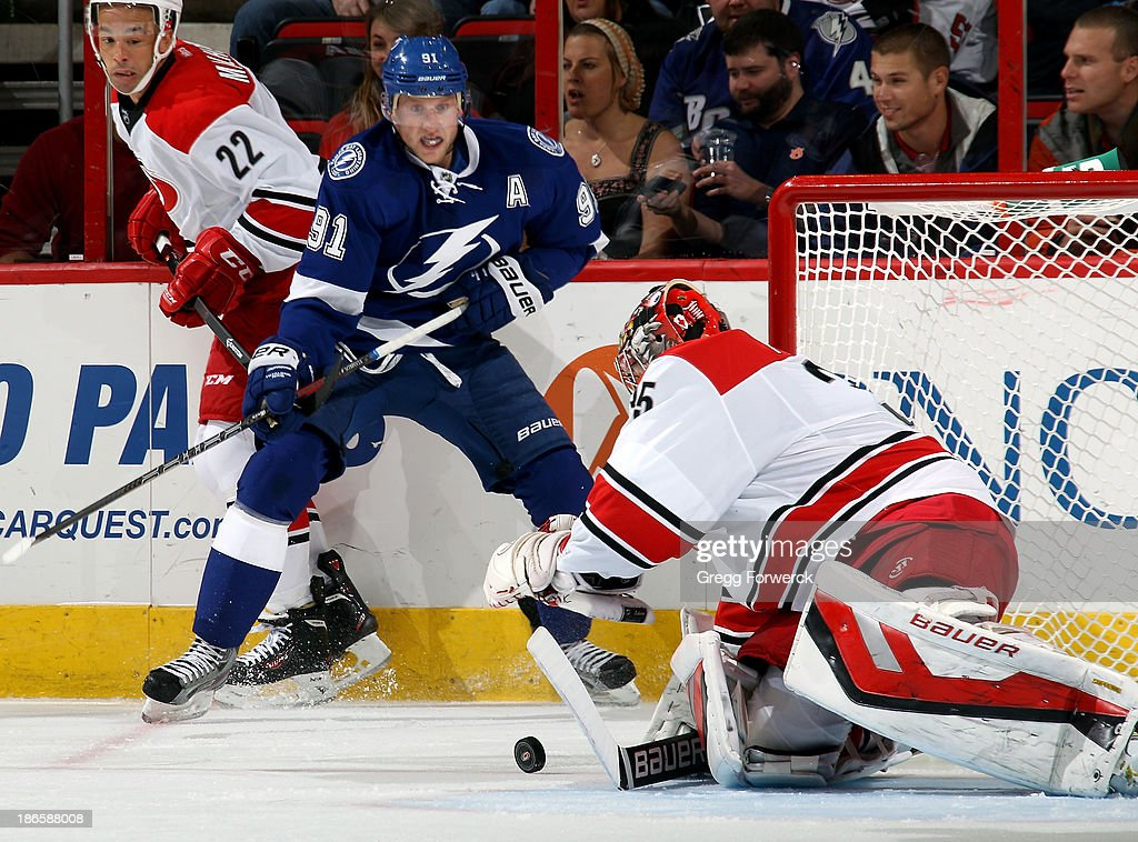 Justin Peters #35 of the Carolina Hurricanes prepares to cover a loose puck as teammate Manny Malhotra #22 and Steven Stamkos #91 of the Tampa Bay Lightning look on during their NHL game at PNC Arena on November 1, 2013 in Raleigh, North Carolina.