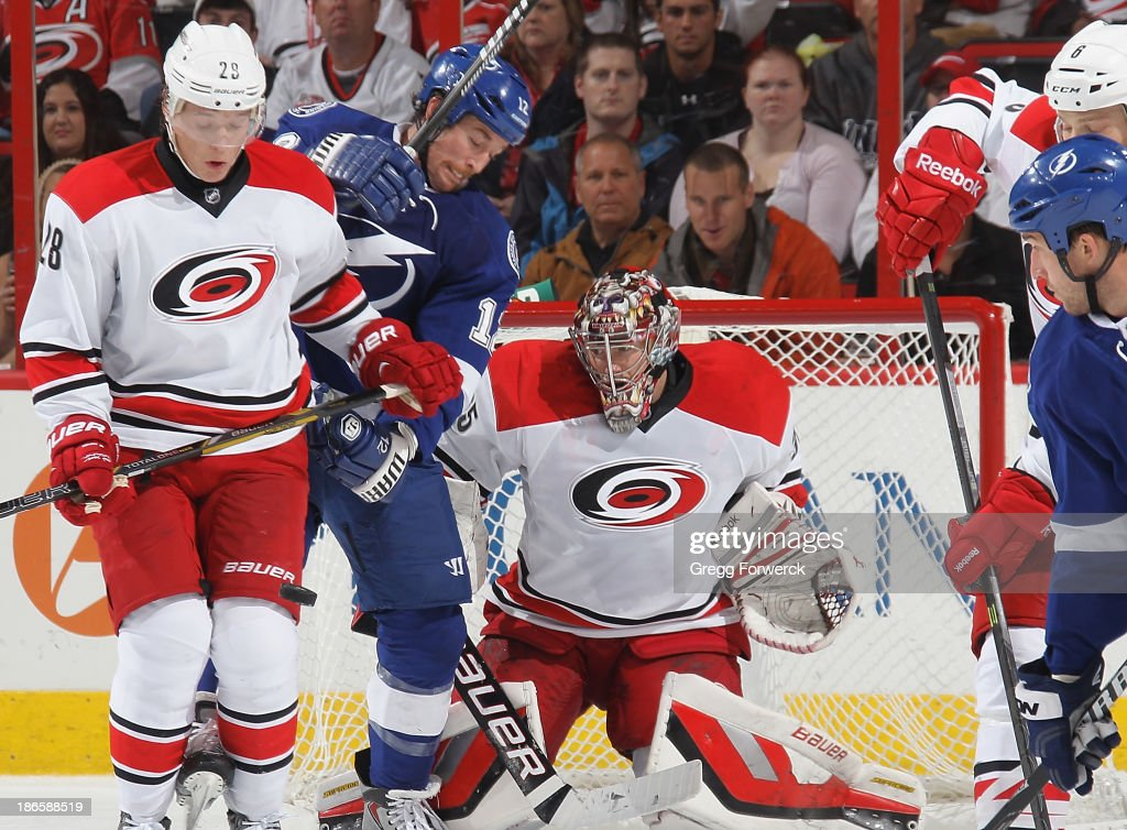 Justin Peters #35 of the Carolina Hurricanes prepars to block a shot as teammate Alexander Semin #28 and Ryan Malone #12 of the Tampa Bay Lightning battle in the crease during their NHL game at PNC Arena on November 1, 2013 in Raleigh, North Carolina.