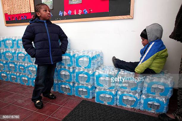 Justin Roberson age 6 of Flint Michigan and Mychal Adams age 1 of Flint wait on a stack of bottled water at a rally where the Rev Jesse Jackson was...