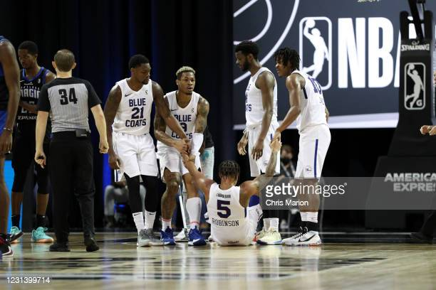 Justin Robinson of the Delaware Blue Coats is helped up by his teammates during the game against the Lakeland Magic on February 26, 2021 at HP Field...